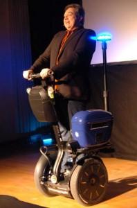Oliver Kalkofe rollt auf einem Elektro-Kart auf die Bühne. <small> Foto: C. Holowaty </small>